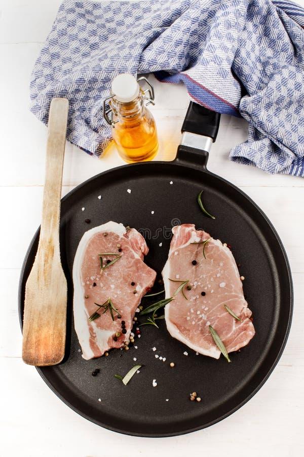 Surowi wieprzowina kotleciki na niecce z rozmarynami, prostacką solą i peppercor, zdjęcia royalty free