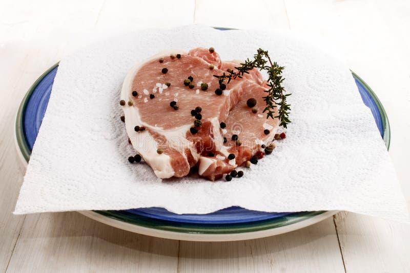 Surowi wieprzowina kotleciki na talerzu z macierzanką, prostacką solą i peppercorn, zdjęcie royalty free