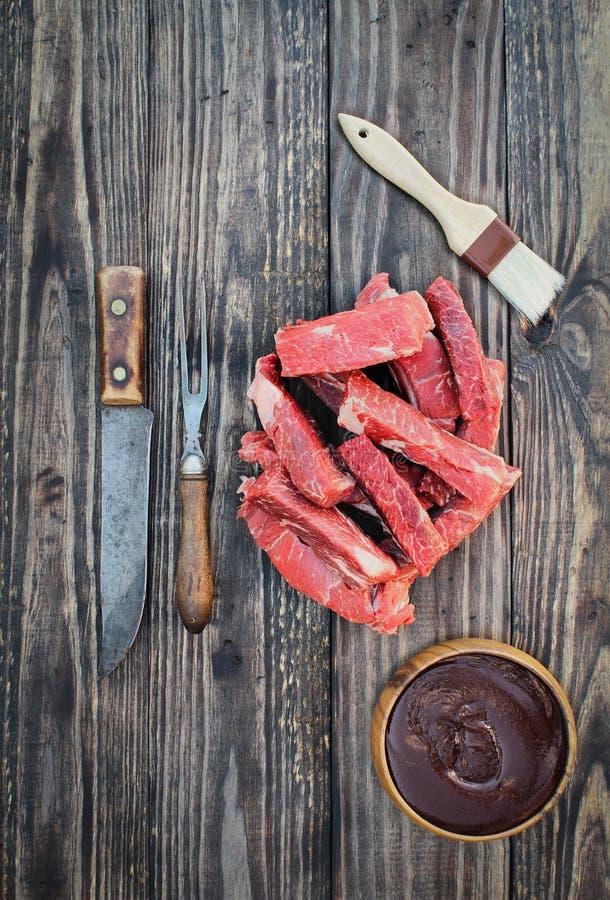 Surowi wołowina ziobro z BBQ muśnięciem nad Drewnianym tłem i kumberlandem obrazy stock