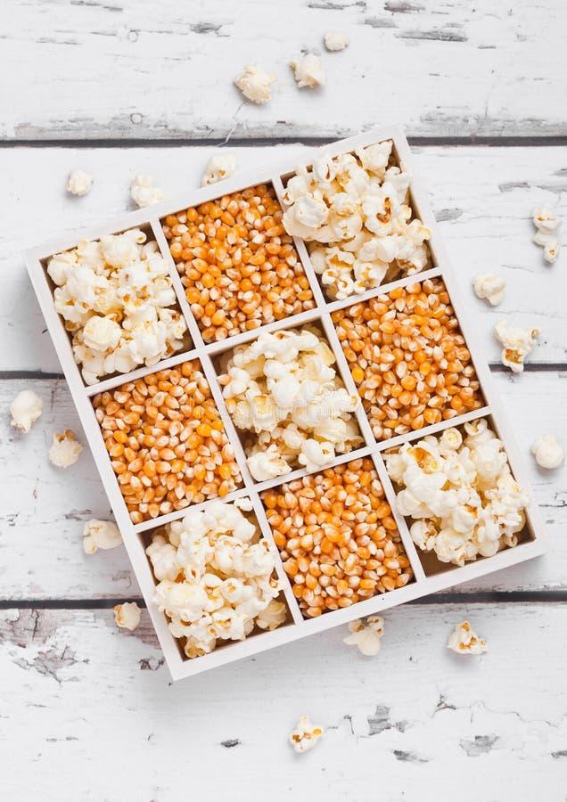 Surowi złoci słodkiej kukurudzy ziarna i popkorn w pudełku zdjęcie royalty free