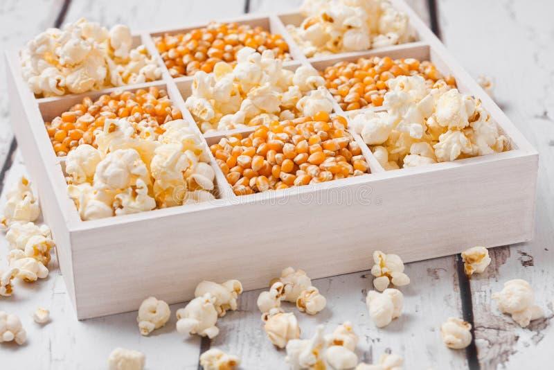 Surowi złoci słodkiej kukurudzy ziarna i popkorn w pudełku fotografia royalty free