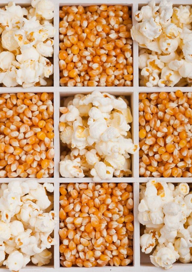 Surowi złoci słodkiej kukurudzy ziarna i popkorn w pudełku zdjęcia royalty free