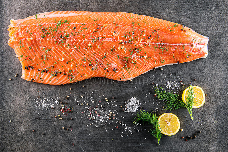 Surowy łososiowy rybi stek z składnikami lubi cytrynę, pieprzu, morze soli i koperu na czerni desce, nowożytny gastronomy w resta zdjęcia stock