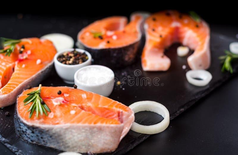 Surowy łososiowy stek na czerń kamieniu, przygotowanym dla gotować zdjęcie royalty free
