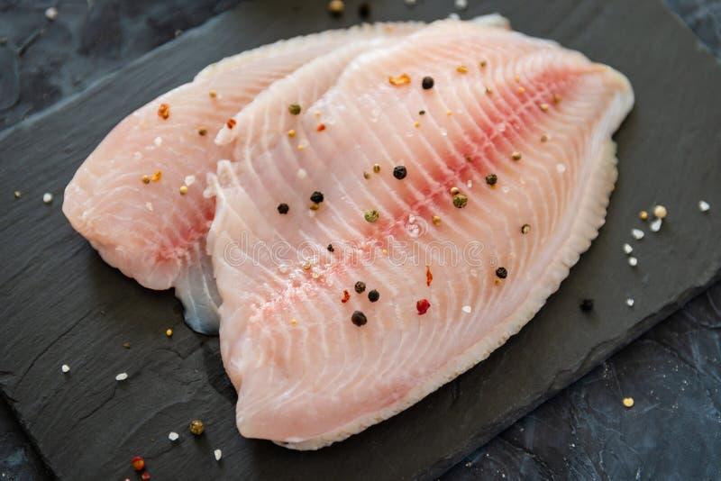Surowy świeży polędwicowy tilapia ryba z pikantność na ciemnym tle z bliska fotografia stock