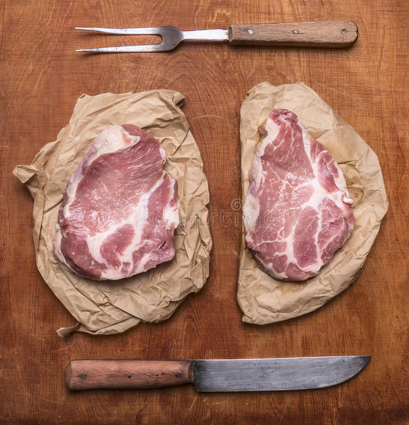 Surowy świeży wieprzowina stek z starym nożem up i mięsnego rozwidlenia tła odgórnego widoku nieociosanym drewnianym zakończeniem zdjęcie royalty free