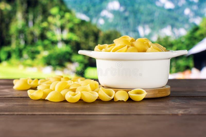 Surowy żółty makaronu conchiglie z kraj naturą zdjęcia royalty free