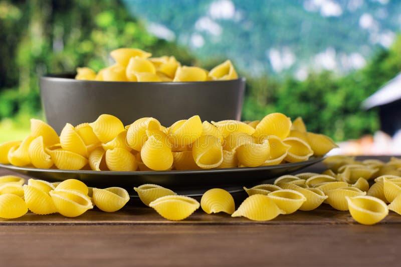 Surowy żółty makaronu conchiglie z kraj naturą zdjęcie royalty free