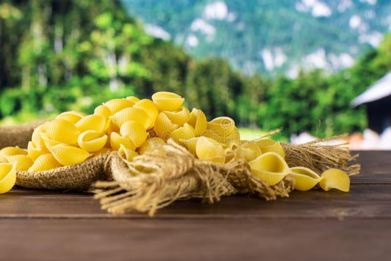 Surowy żółty makaronu conchiglie z kraj naturą obrazy royalty free