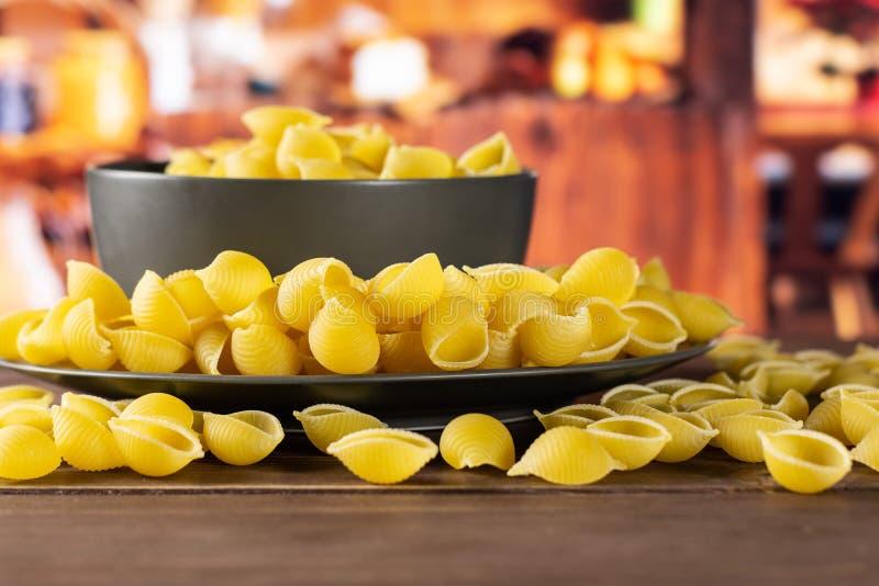 Surowy żółty makaronu conchiglie z nieociosaną kuchnią fotografia stock