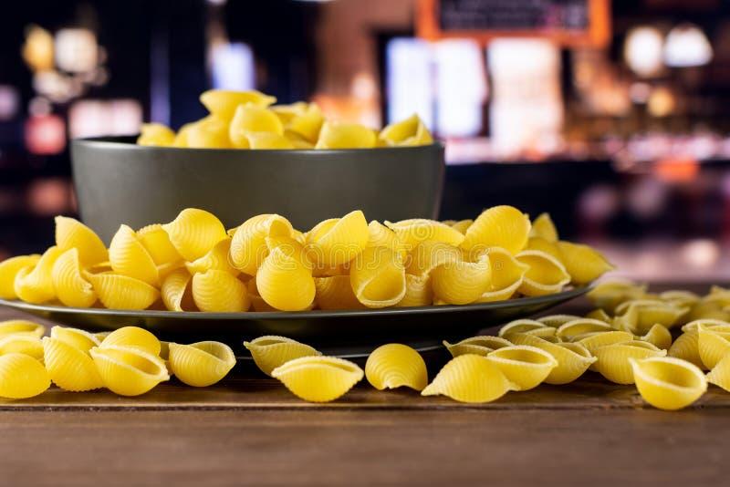 Surowy żółty makaronu conchiglie z restauracją zdjęcie royalty free