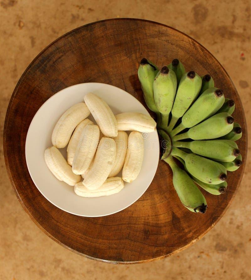Surowy banan w naczyniu na drewnianym stole zdjęcie stock