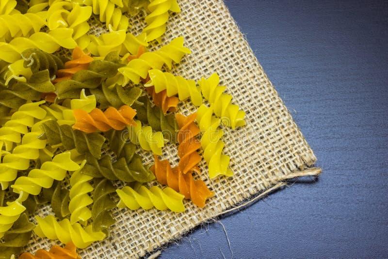 Surowy barwiony fusilli makaron na burlap z zakończeniem zdjęcie royalty free