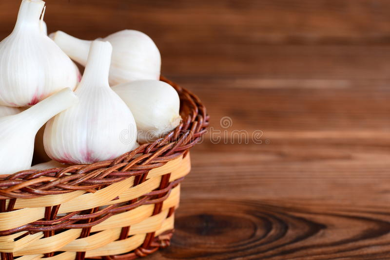 Surowy biały czosnek w łozinowym koszu na brown drewnianym tle z pustym dla teksta i Naturalny młody czosnek żarówek żniwo fotografia royalty free