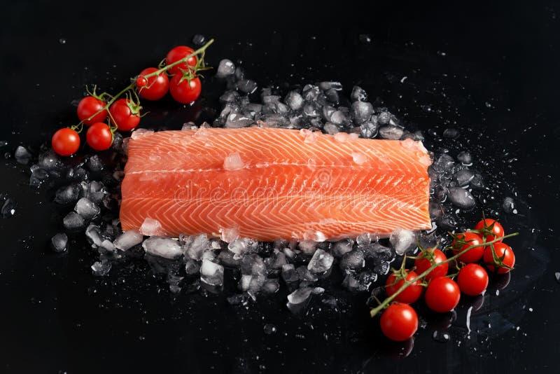 Surowy cały łosoś polędwicowy na odłupanym lodzie na czerni tła dowcipu h pomidorach na sprig na widok zdjęcia royalty free
