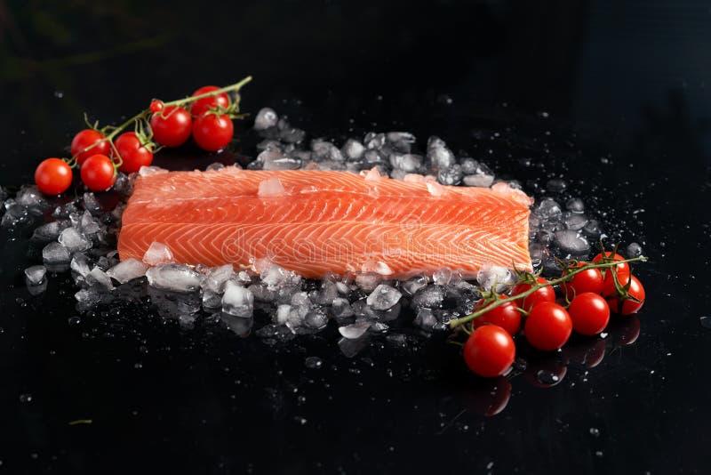 Surowy cały łosoś polędwicowy na odłupanym lodzie na czerni tła dowcipu h pomidorach na sprig na widok fotografia stock
