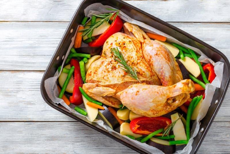 Surowy cały kurczak z kolorowymi kawałkami pieprze, grule Cl obraz stock