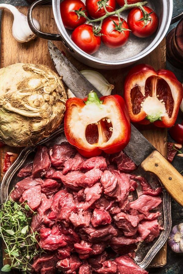 Surowy diced wołowiny mięso, warzywo składnik, kuchenny nóż i kucharstwo, puszkujemy Gulaszu lub goulash przygotowanie fotografia royalty free