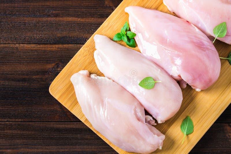 Surowy kurczak przepasuje na tnącej desce przeciw tłu drewniany stół Mięśni składniki dla gotować Opróżnia miejsce dla obraz stock