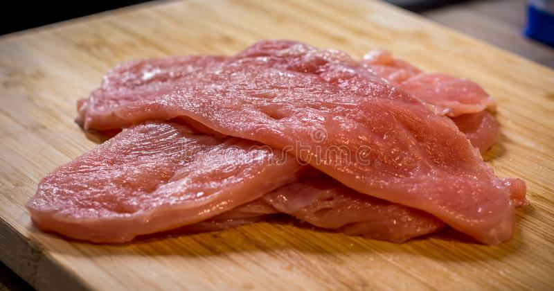 Surowy kurczaka mięso umieszczający na drewnianym biurku Bezkostny uncooked mięsień przygotowywający dla gotować obraz stock
