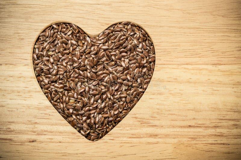 Surowy lnów ziaren linseed serce kształtujący obrazy stock