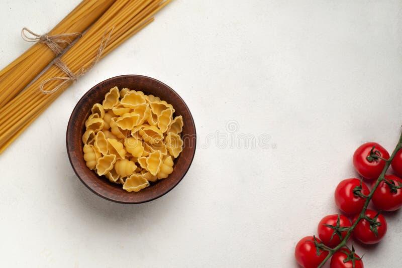 Surowy makaron w talerzu obok długiego makaronu i gałązka pomidorów wiśniowych symetria górnego widoku wolna przestrzeń obrazy royalty free