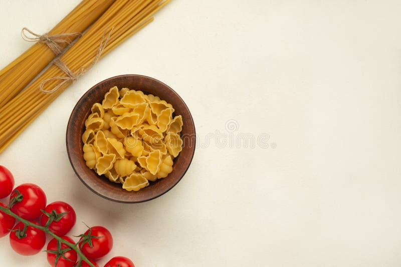 Surowy makaron w talerzu obok długiego makaronu i gałązka pomidorów wiśniowych symetria górnego widoku wolna przestrzeń zdjęcie royalty free