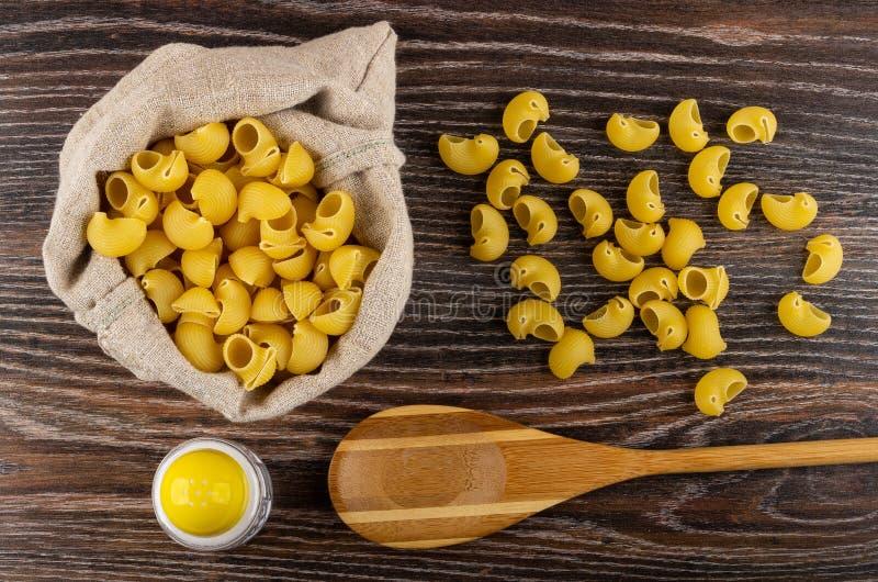 Surowy makaronu lumache w torbie, sól, łyżka, rozrzucony makaron na stole Odgórny widok fotografia stock