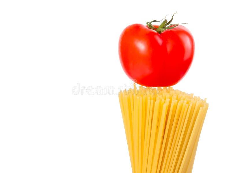 Surowy makaronu spaghetti z pomidorem na wierzchołku na białych półdupkach obrazy royalty free