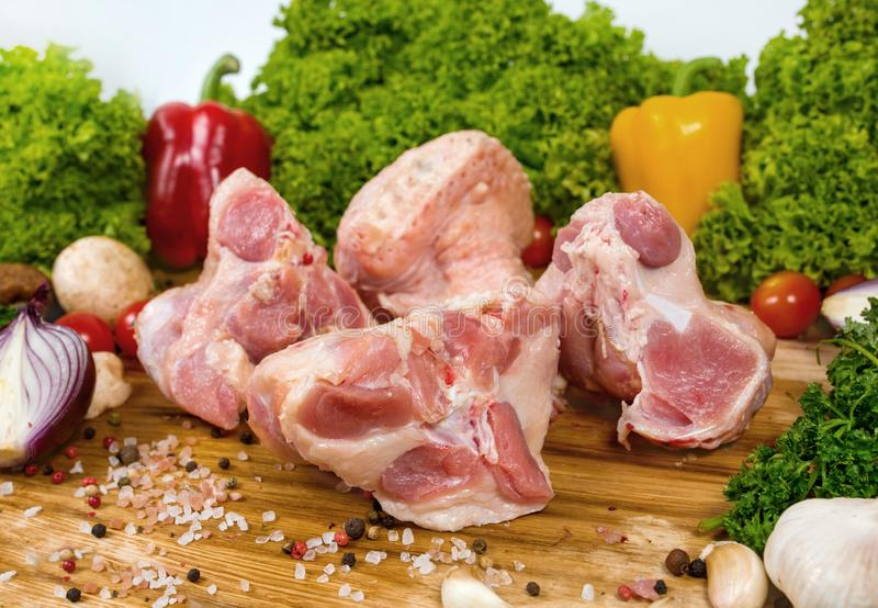 Surowy mięso, indyczy mięso na tnącej drewnianej desce z czereśniowymi pomidorami, sałata opuszcza, czosnek, chili pieprz, rozmar obrazy stock