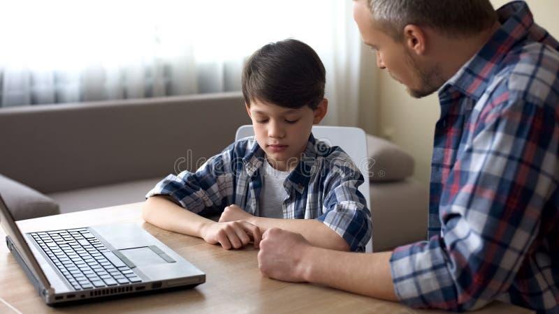 Surowy ojciec łaja jego małego syna dla komputerowego nałogu, rodzinny problem obrazy stock