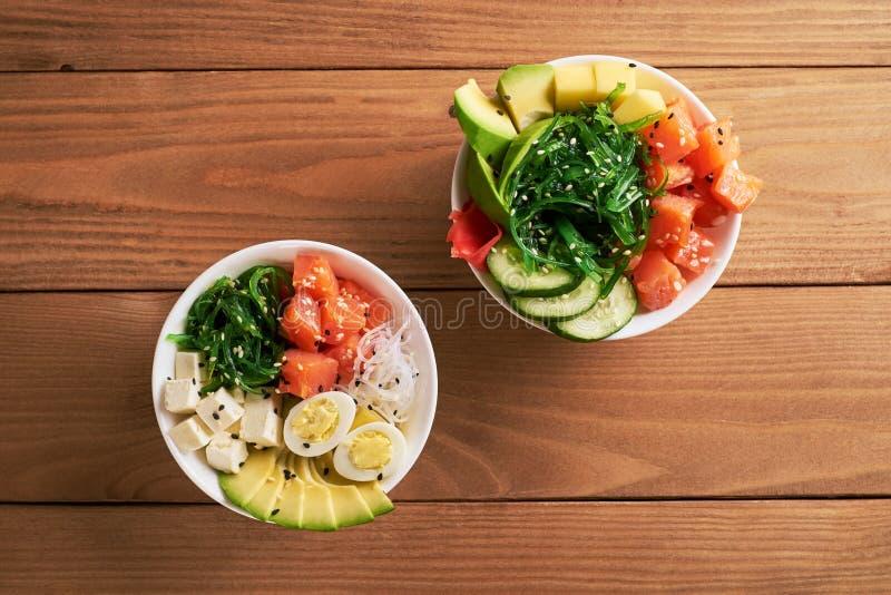 Surowy Organicznie potrącenie puchar z z ryż, avocado, łosoś, mango, ogórki, chuka sałatka, przepiórek jajka, słodkie cebule dwa  zdjęcie stock