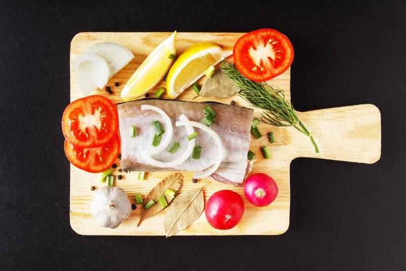 Surowy rybi mięso, odgórny widok z zbliżeniem na tnącej desce, organicznie rzodkwi, cytryny, cebuli i pikantności, Świezi natural obrazy royalty free