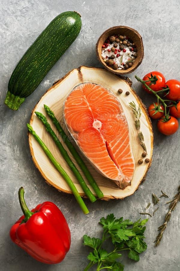 Surowy rybiego stku ?oso? z ?wie?ymi warzywami, asparagusem, zucchini, s?odkimi pieprzami, pomidorami, ziele i pikantno?? na szar fotografia stock