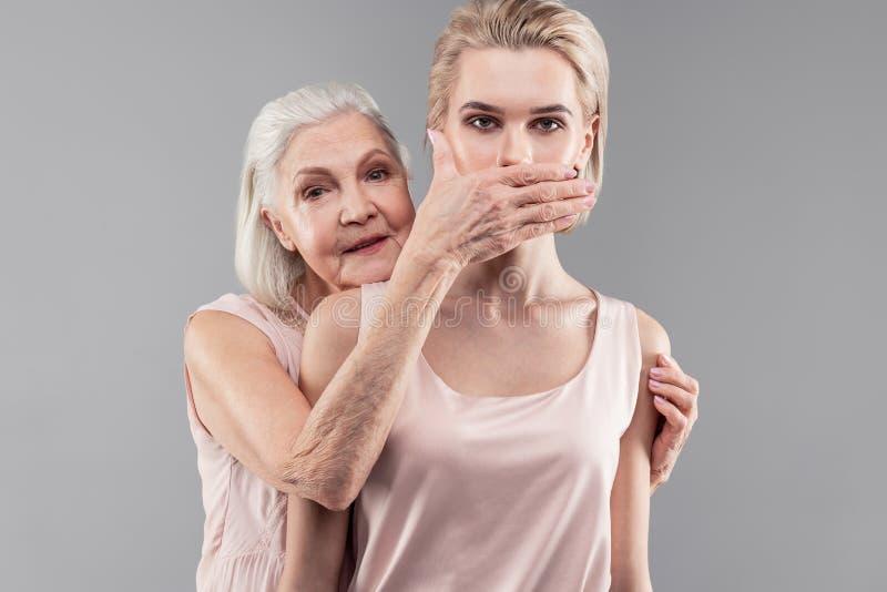Surowy staromodny siwowłosy macierzysty nakrywkowy usta jej córka fotografia stock