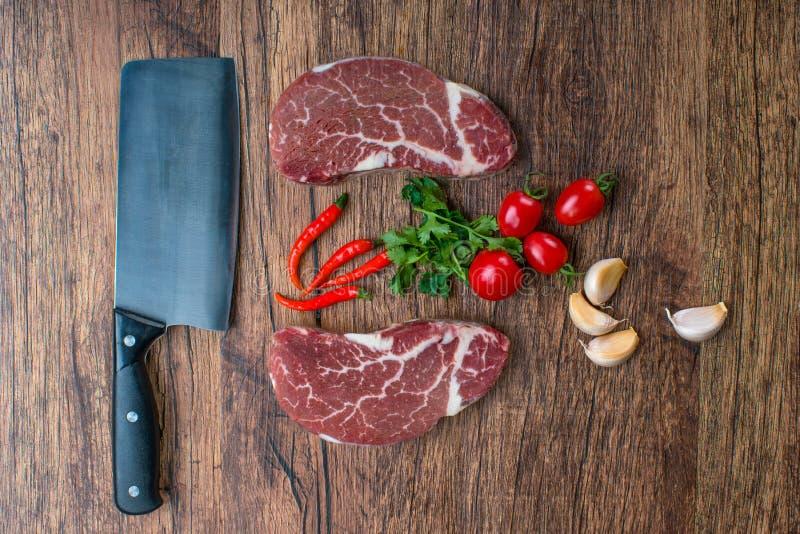 Surowy stek z pikantność na drewnianym tle zdjęcie royalty free