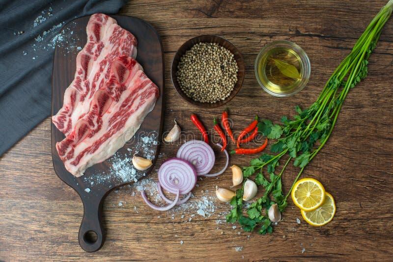 Surowy stek z pikantność na drewnianym tle zdjęcie stock