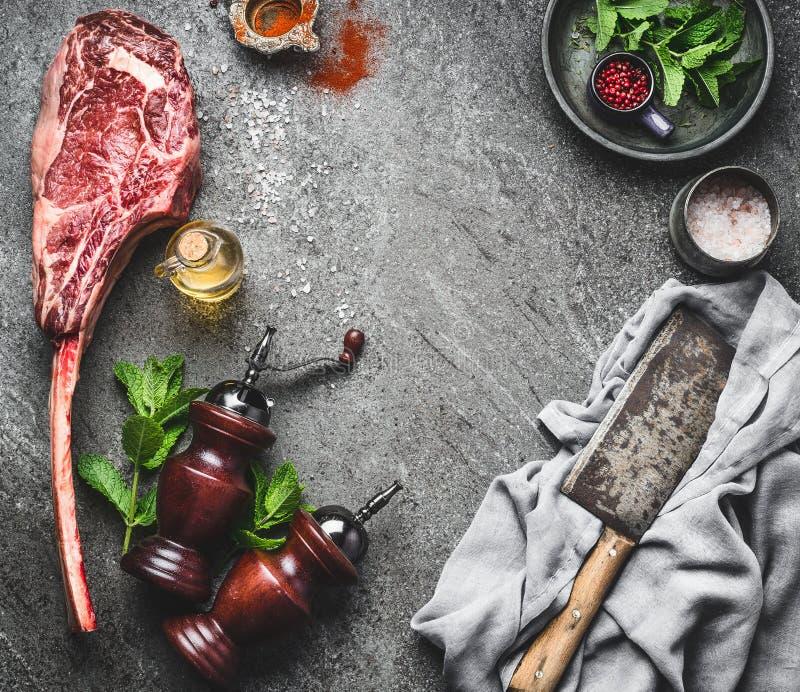 Surowy tomahawk wołowiny stek z mięsnym cleaver, condiment i świezi ziele na ciemnym wieśniaka betonie, zgłaszamy tło, odgórny wi obraz royalty free