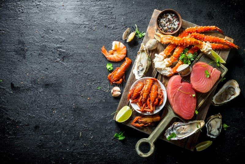 Surowy tuńczyka stek, owoce morza na drewnianej tacy i obraz royalty free