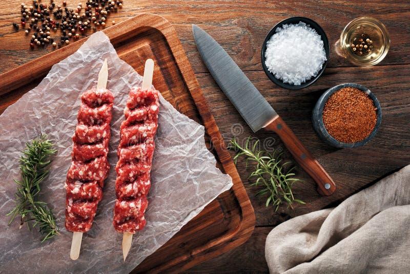 Surowy turecczyzny Urfa kebab na białym kucharstwo papierowym i drewnianym rozcięcie stole Dekorujący z ziele, pikantność i nożem obrazy royalty free