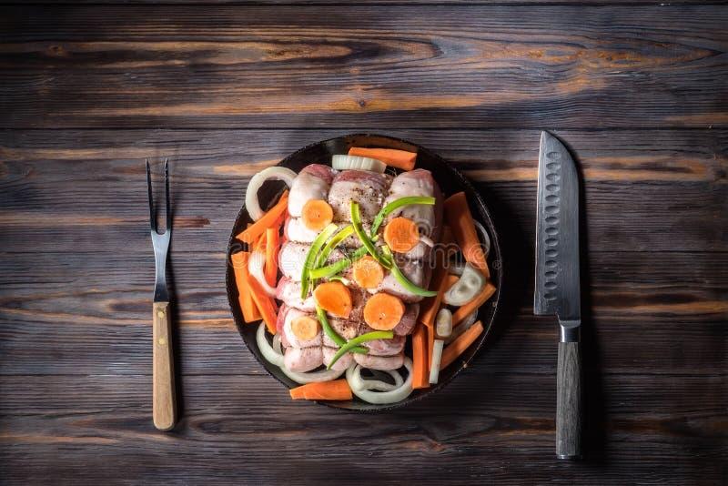 Surowy wieprzowina kotlecik marynował mięsną rolkę z asortowanymi warzywami zdjęcia royalty free