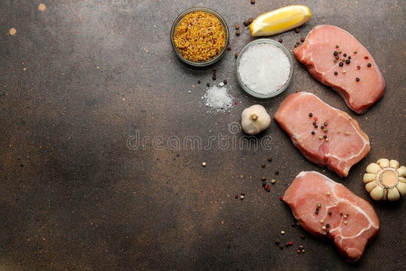Surowy wieprzowina stek, mięso i składniki dla, gotować, pikantność, ziele i warzyw na ciemnym tle, Odg?rny widok Przestrze? dla  obrazy royalty free