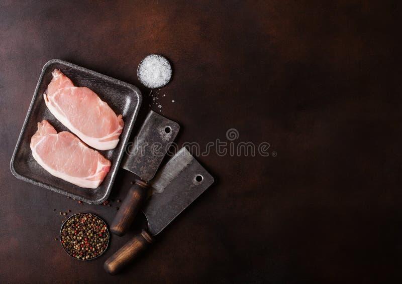 Surowy wieprzowiny loin sieka w plastikowej tacy z soli, pieprzu i rocznika mi?snymi siekierkami na o?niedzia?ym tle Przestrze? d zdjęcia stock