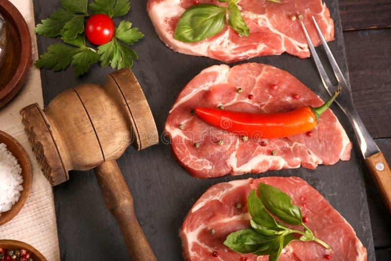 Surowy wieprzowiny mi?sa stek z warzywami, sol?, rozmarynami i pikantno?? gotuje nad kamienia sto?em, Odg?rny widok obrazy stock