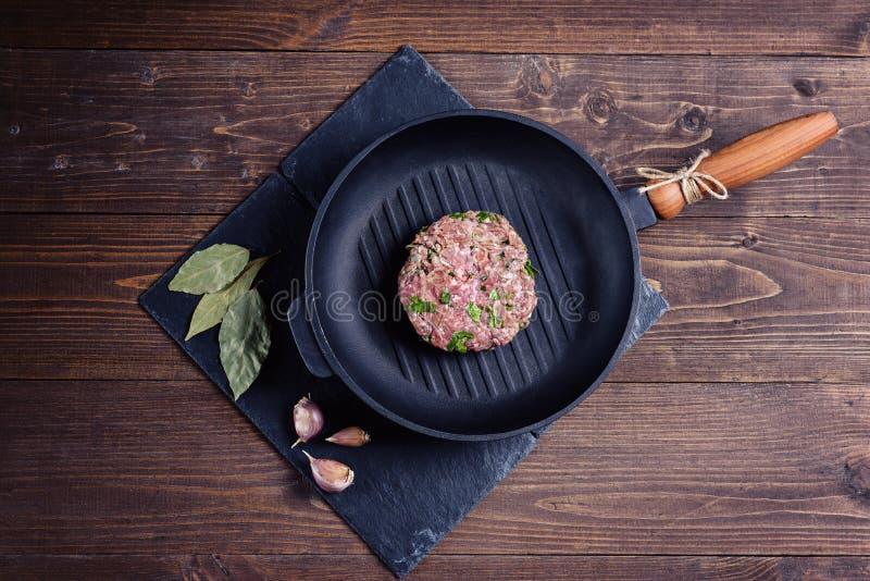Surowy wołowina plasterek z ziele na grill niecce na popielatym kamieniu z czosnkiem i Podpalanym liściem na brown drewnianym tle fotografia stock