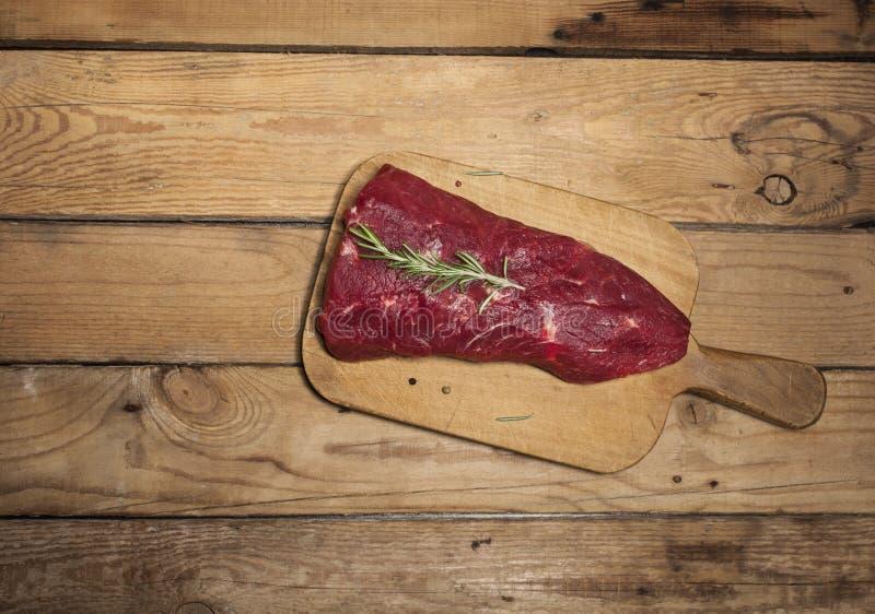 Surowy wołowina stek na tnącej desce z rozmarynami i pikantność zdjęcie stock