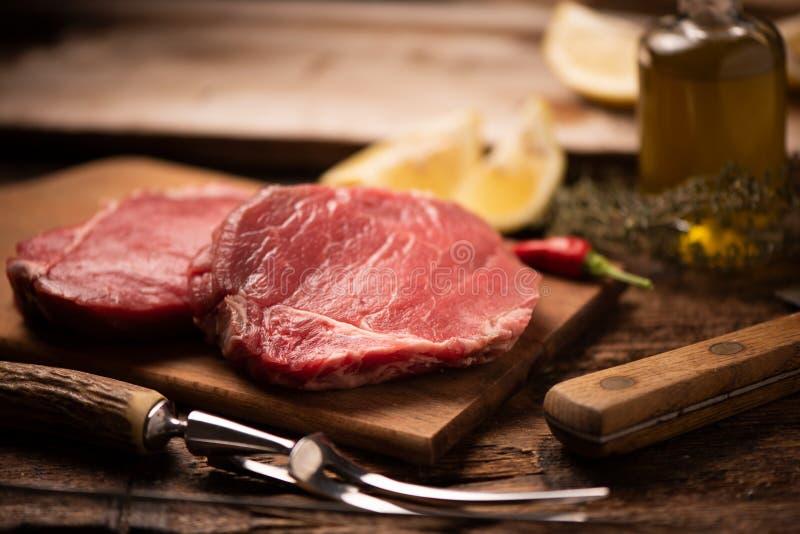Surowy wołowina stek, pikantność na drewnianej tnącej desce i obraz stock
