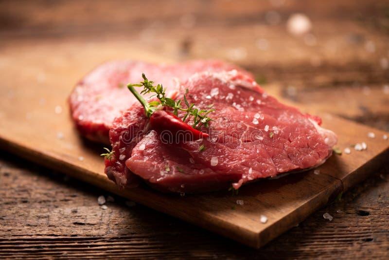 Surowy wo?owina stek, pikantno?? na drewnianej tn?cej desce i fotografia royalty free