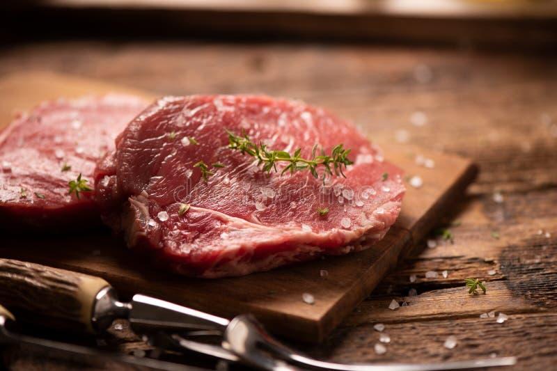 Surowy wo?owina stek, pikantno?? na drewnianej tn?cej desce i zdjęcia royalty free