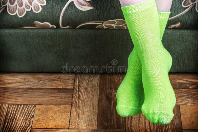 Surplomb de pied du sofa dans les chaussettes vertes photographie stock libre de droits